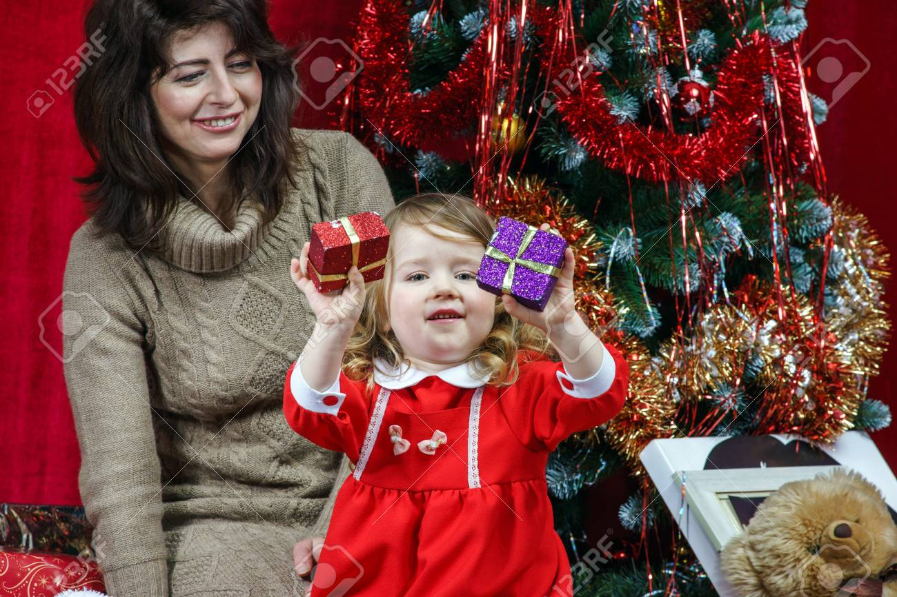 Mother with little daughter finding christmas gifts over the tree Stock Photo - 25151178