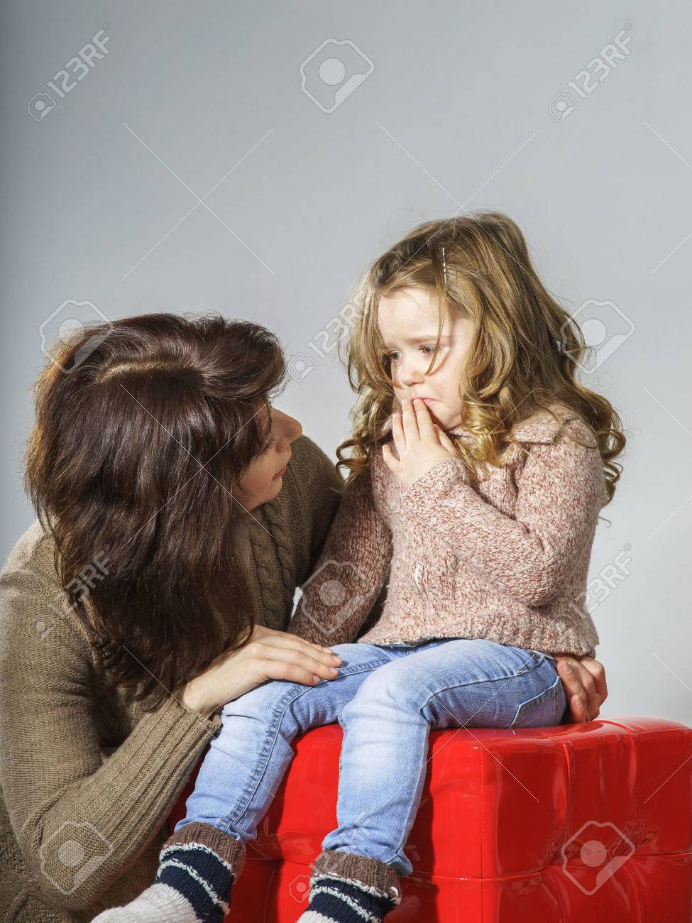 Mother reassuring little daughter. She is distracted and crying - 25152203