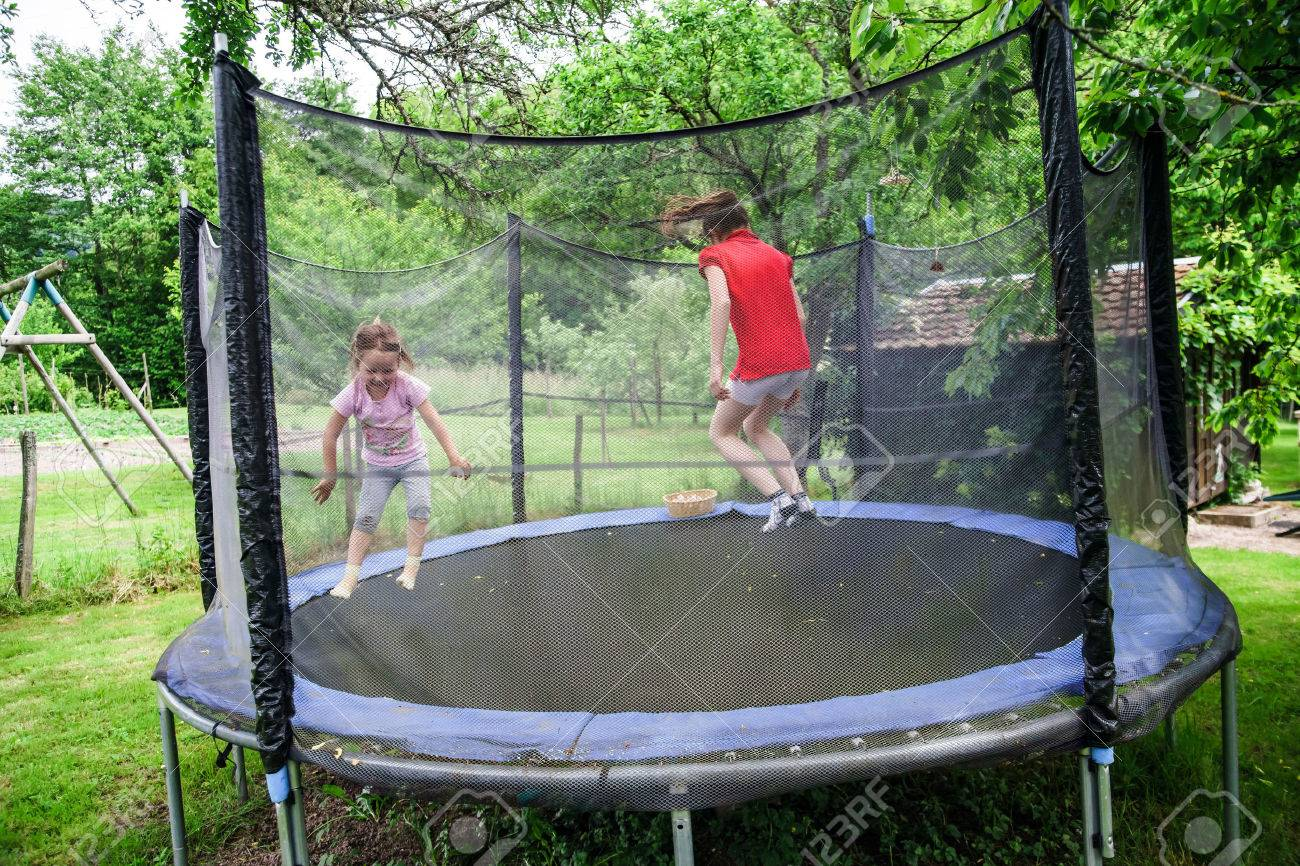 Two happy sisters on trampoline, children leisure - 28884393