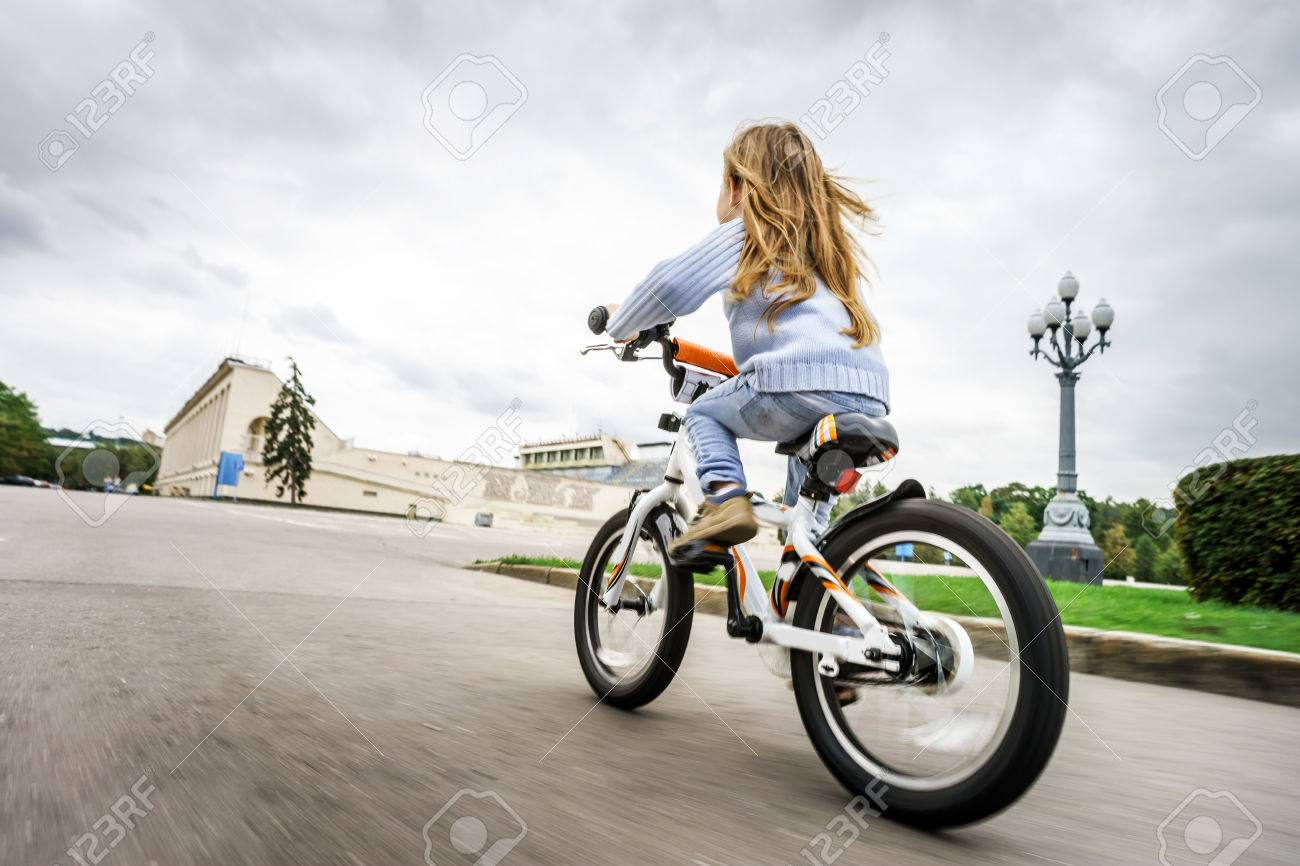 Cute little girl riding fast by bicycle in public park - 31345854