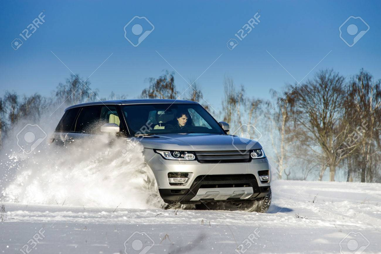 Powerful 4x4 offroader car running on snow field winter day, transport concept - 37767987