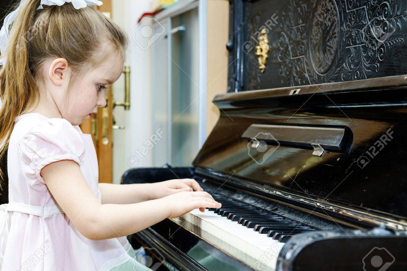 Cute little girl playing old piano at home lesson - 37878509