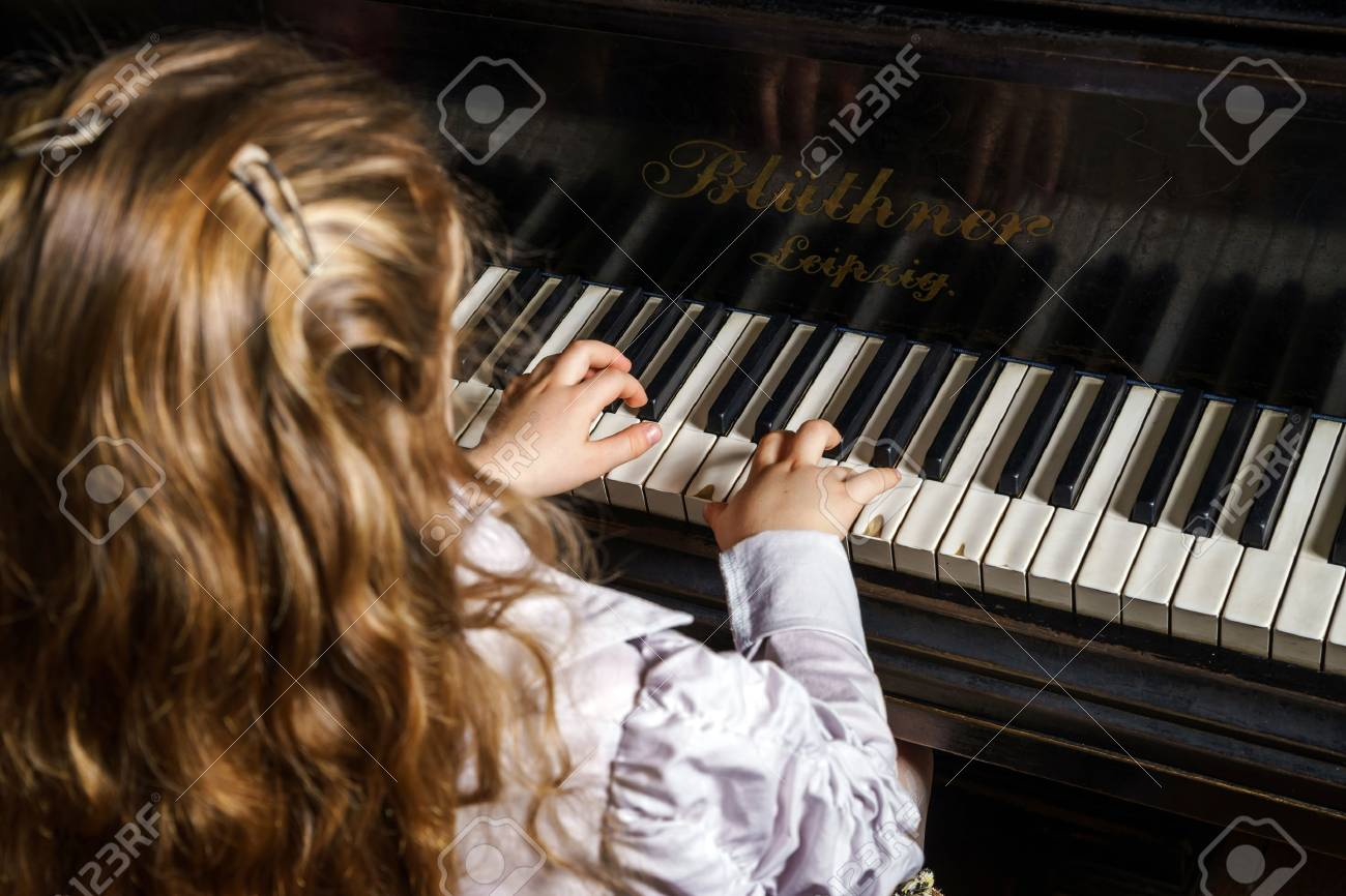 Cute little girl playing grand piano in music school, childhood concept - 39503376