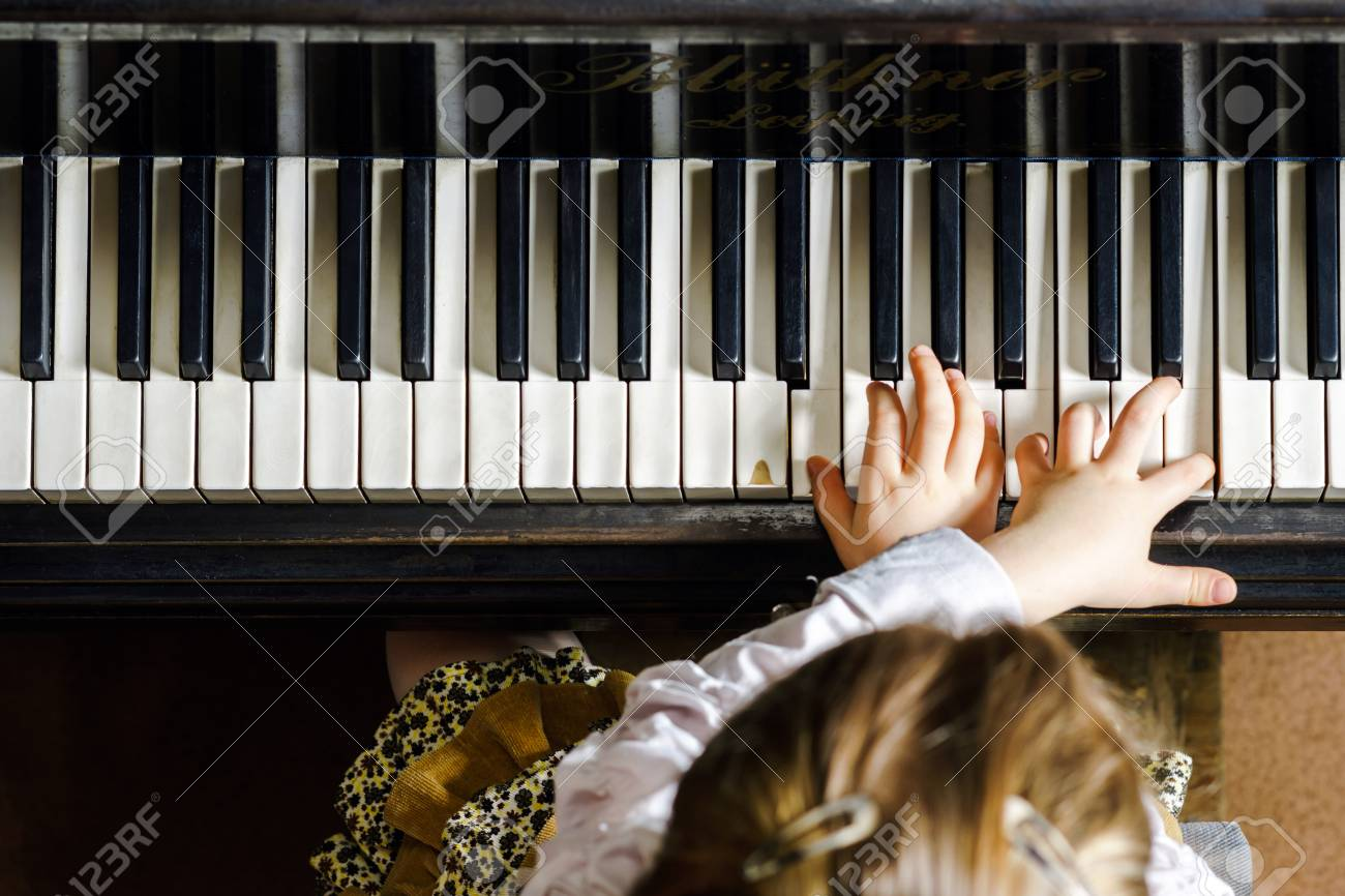 Cute little girl playing grand piano in music school, childhood concept - 39503387