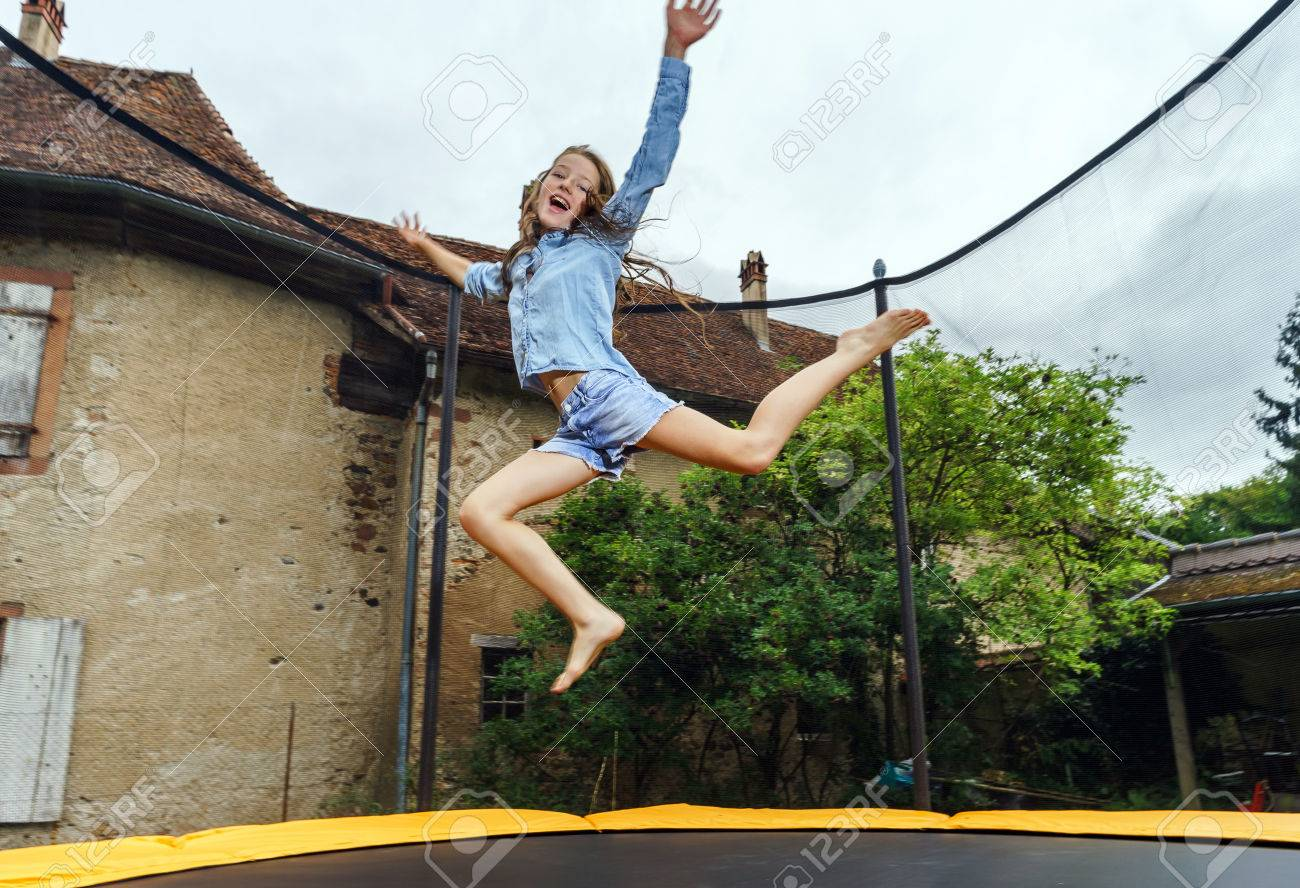Cute teenage girl jumping on trampoline, childhood concept - 43761475