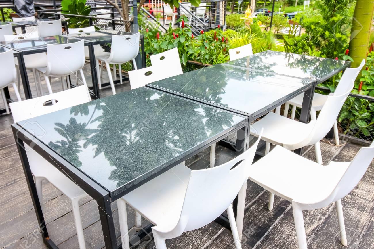 Mesa de comedor con silla en el exterior con jardín verde campo