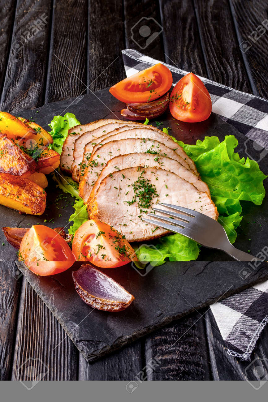 Sliced baked ham with fresh tomatoes on a stone plate in a rustic style - 159667965