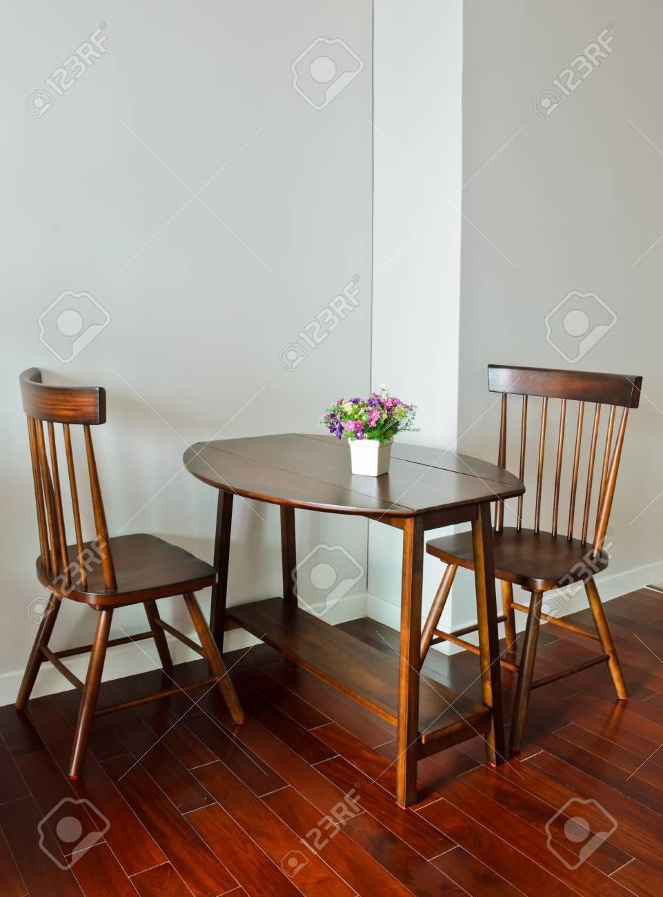Mesa de comedor pequeña con maceta de flores artificiales