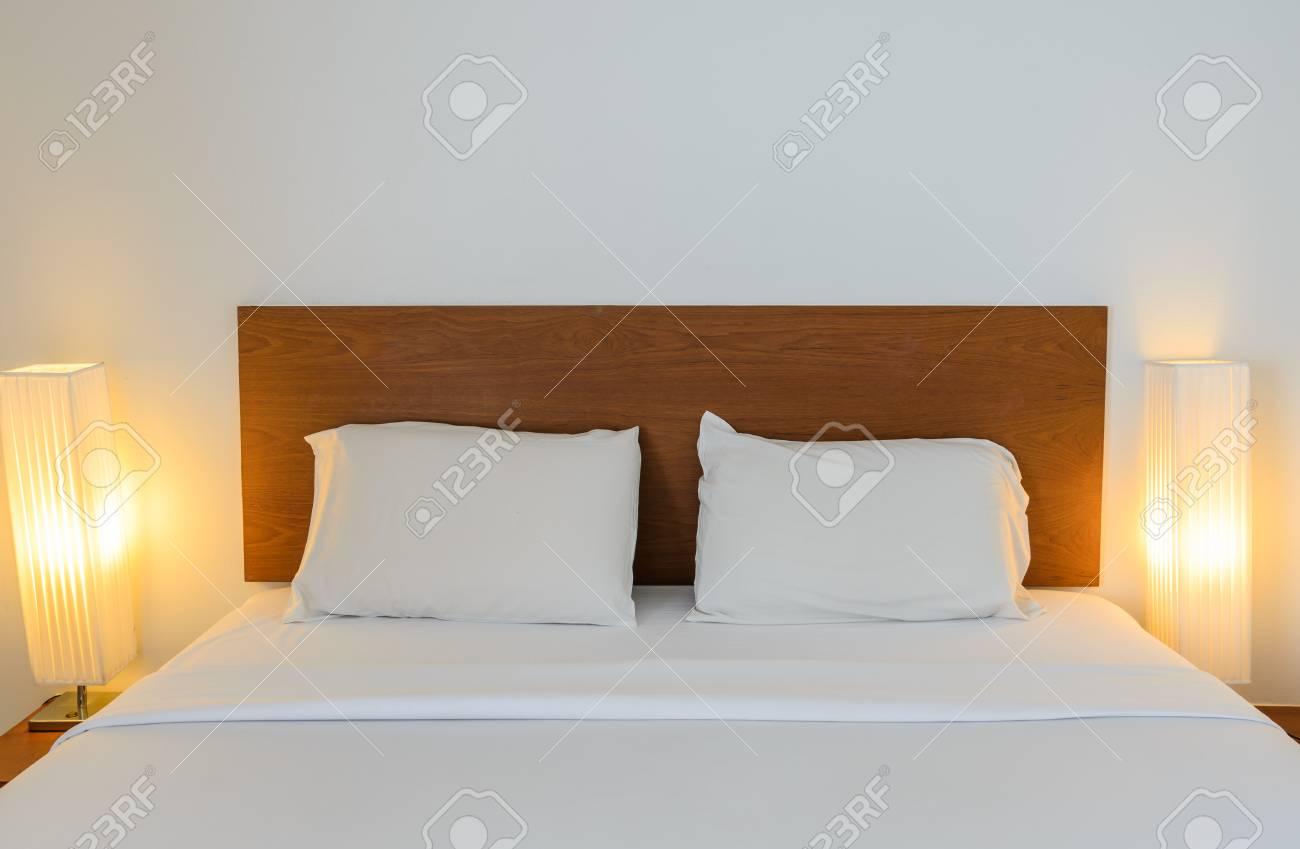 White bedroom with tidy bed and illuminated table lamps