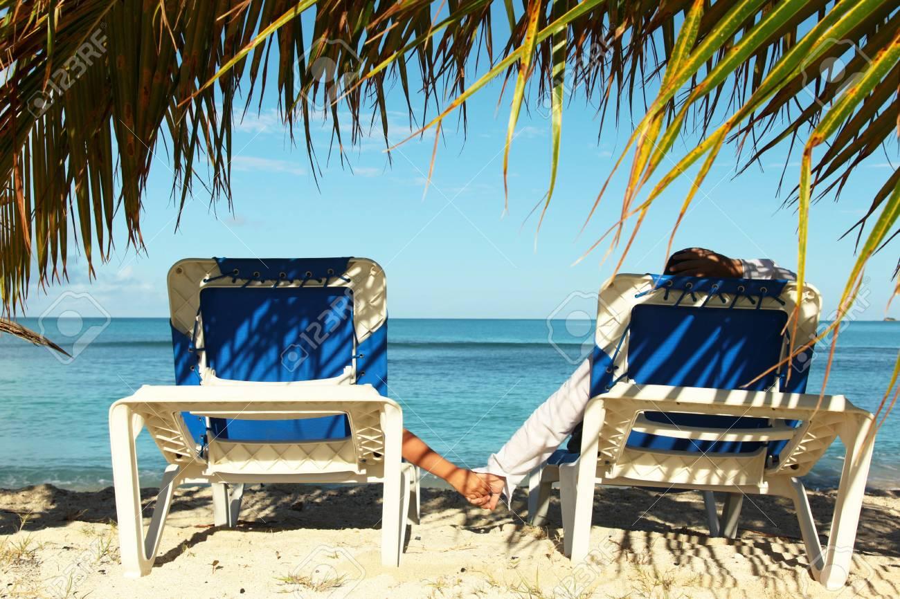 Paar Auf Den Sonnenliegen Genießen Urlaub Am Strand Lizenzfreie