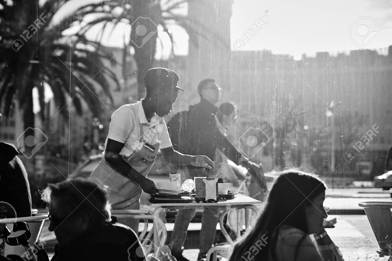 Black and white photography lisbon portugal january 2018 an african american woman waiter in orange uniform