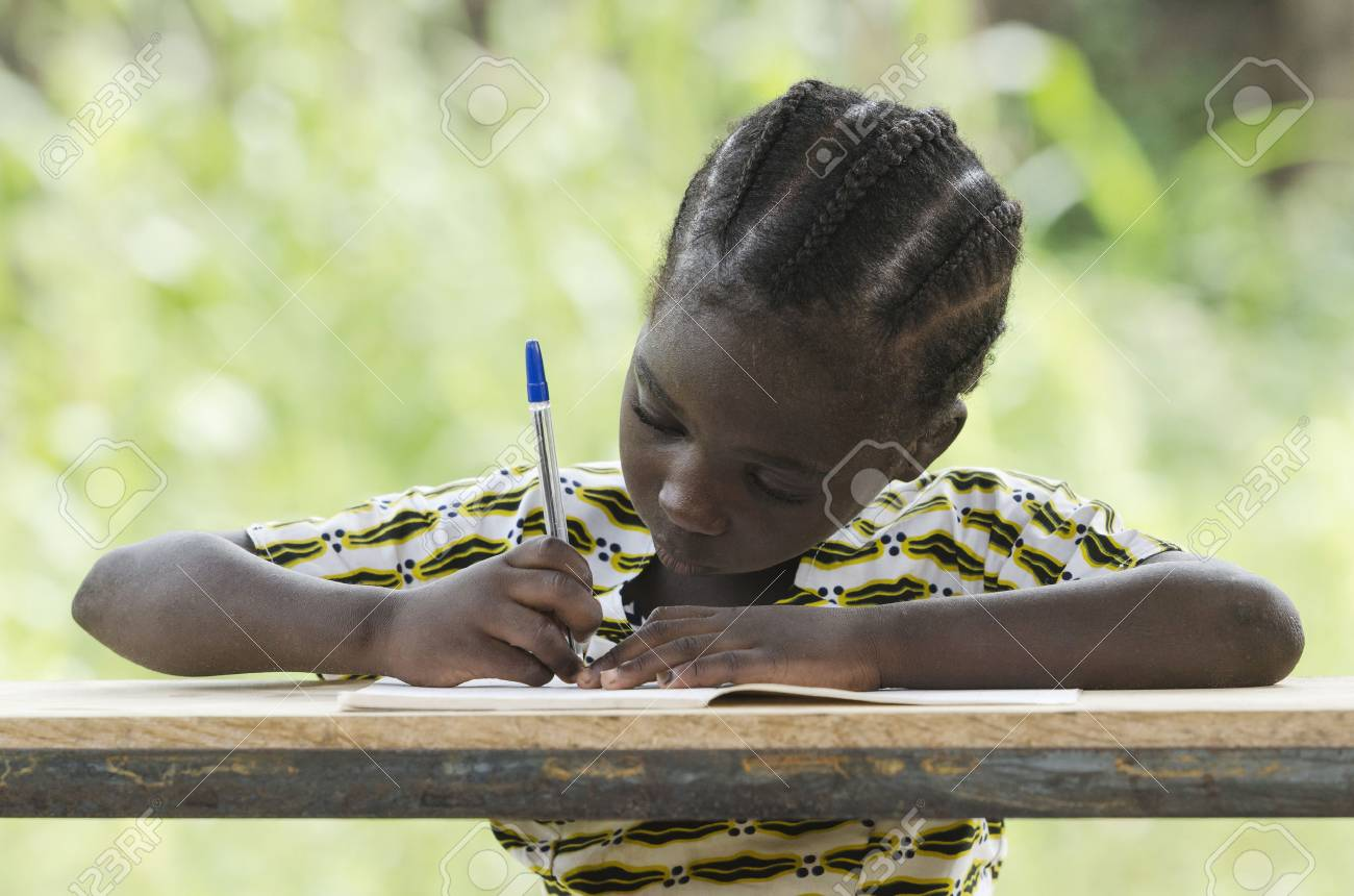 Young girl sitting at table and writing on paper with color pen - 73610536