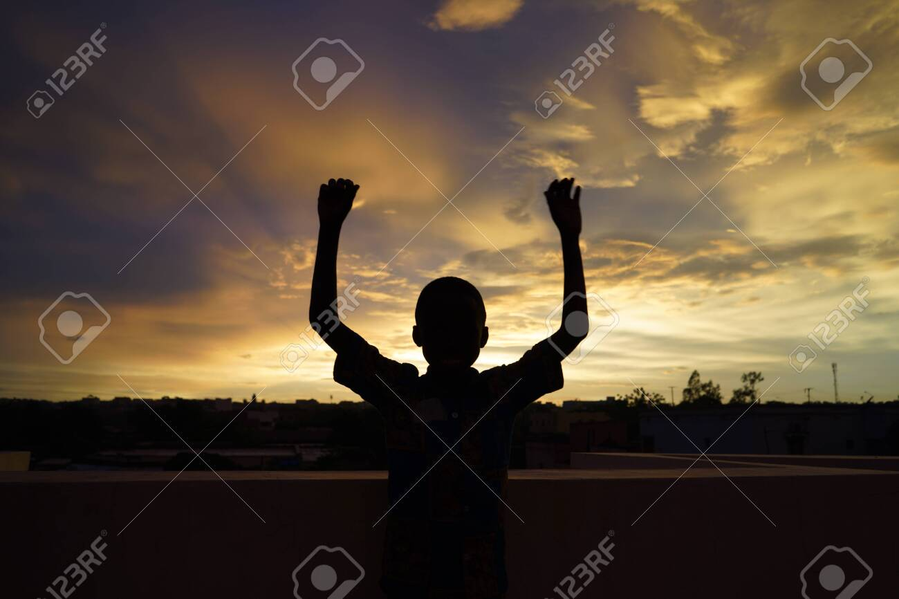 Handsome African Boy Waves in front of Evening Sun - 142144195