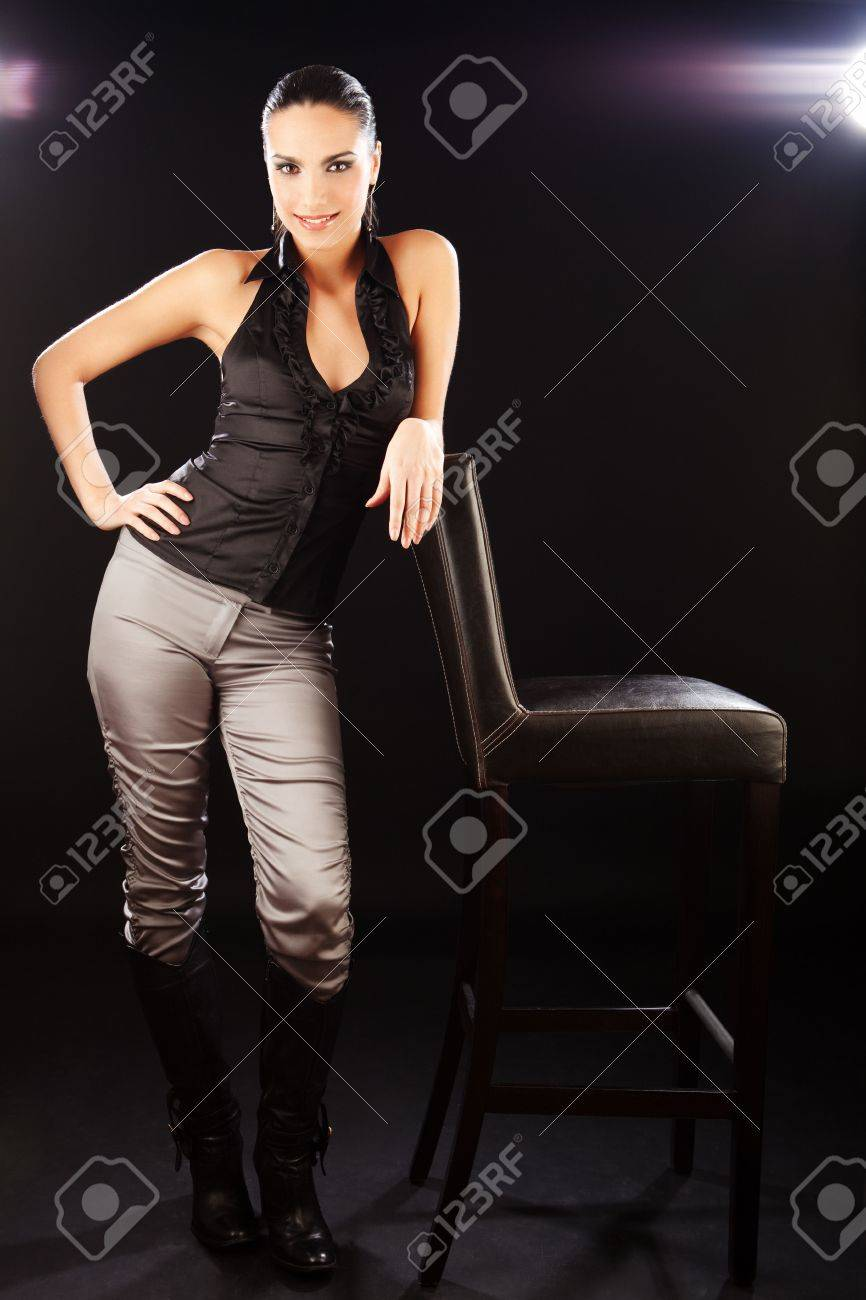 Brunette fashion girl standing beside the bar chair and looking at camera. Stock Photo - 6458878