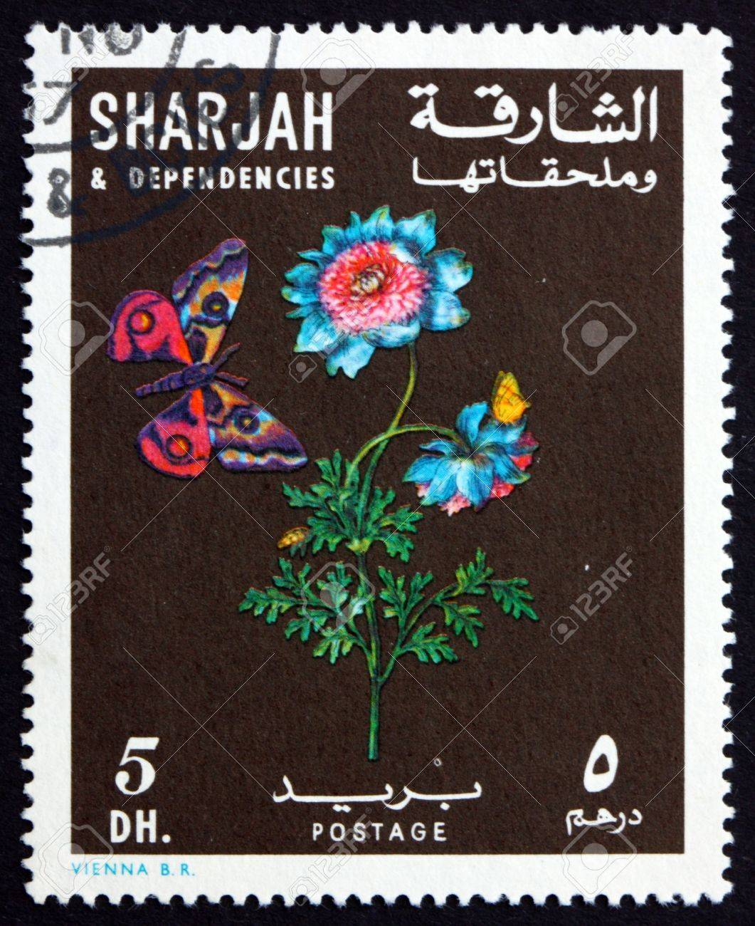 SHARJAH - CIRCA 1967: a stamp printed in the Sharjah UAE shows Anemone, Anemone Coronaria, Flower and Butterfly, circa 1967 Stock Photo - 16896078