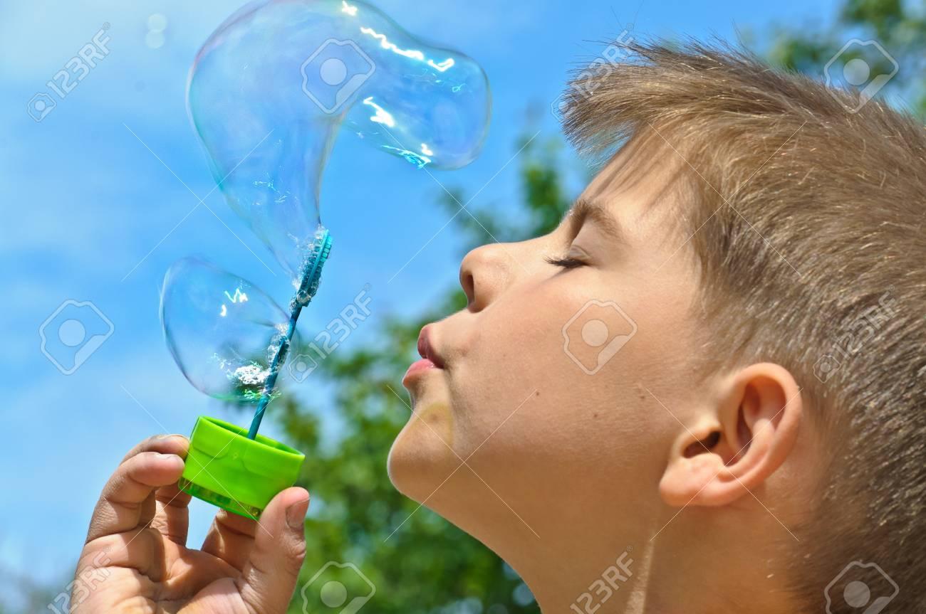 A little boy blows bubbles. Background sky. Stock Photo - 9571673
