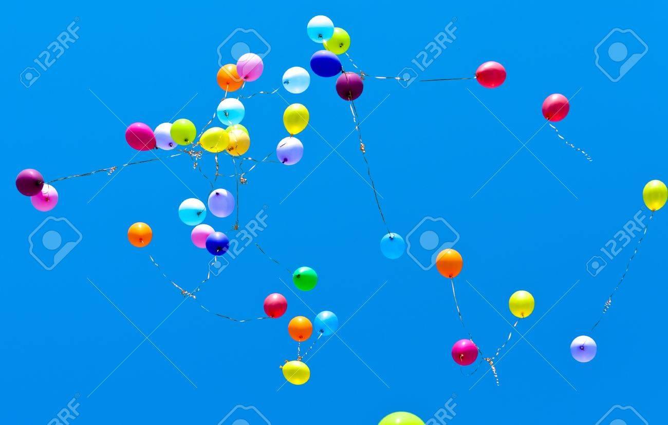 Many balloons fly into the blue sky - 9615640