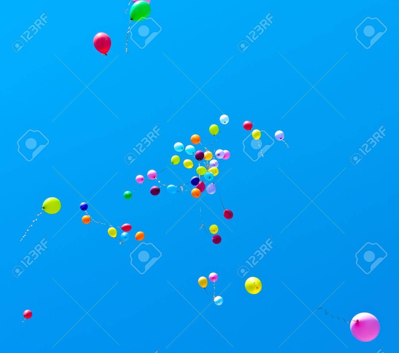 Many balloons fly into the blue sky - 9615632