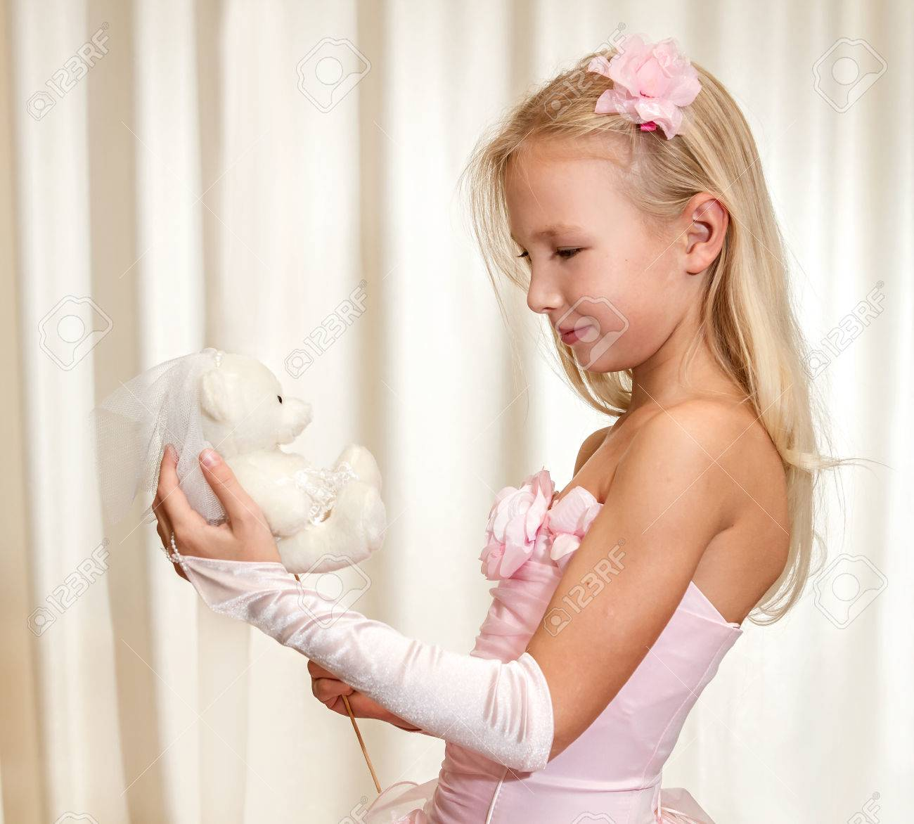Little Girl Plays With Wedding Teddy-bear. Girl Is Wearing Pink ...