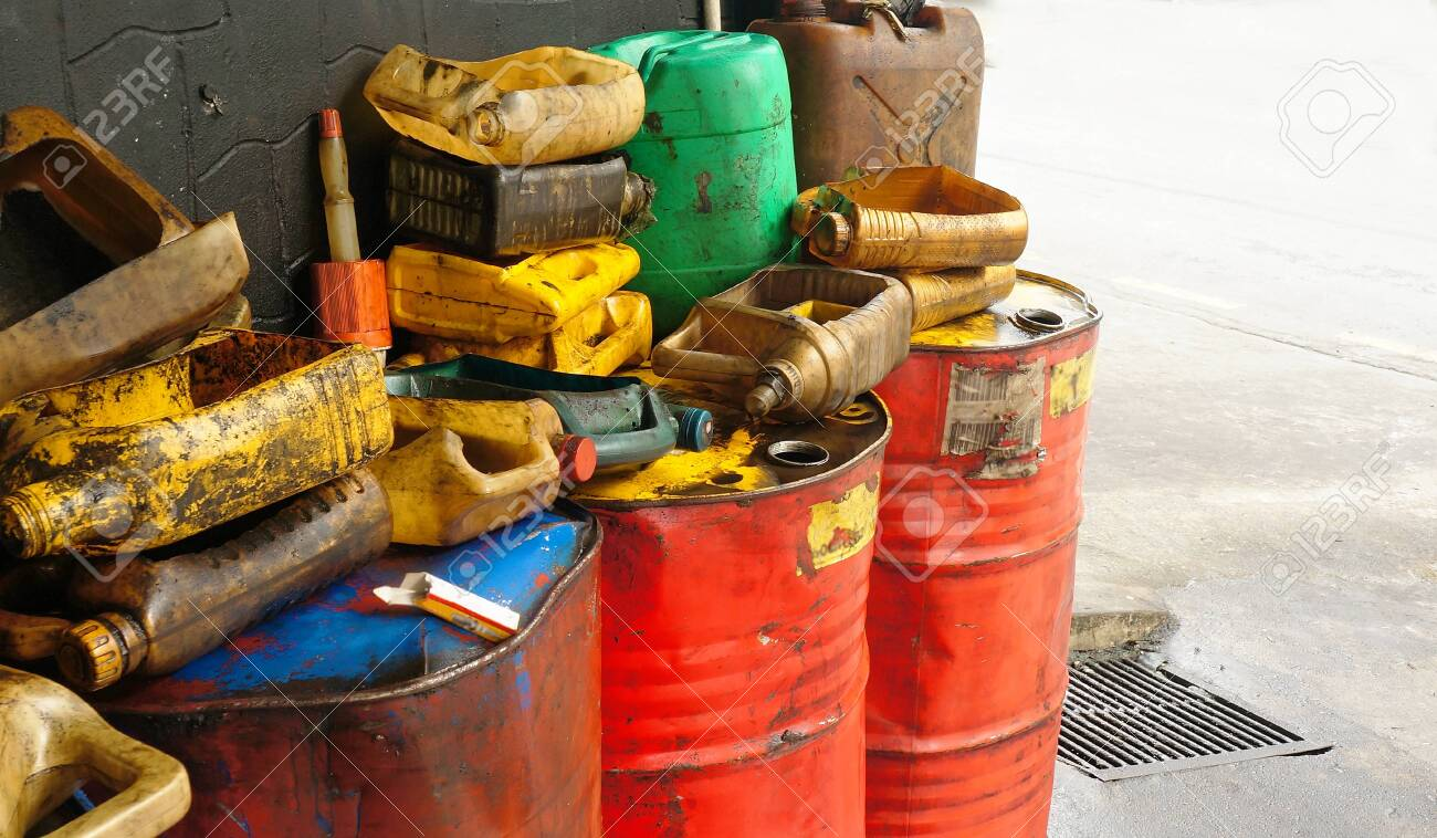 Dirty & oily plastic canisters on waste oil barrels tank - 118683788