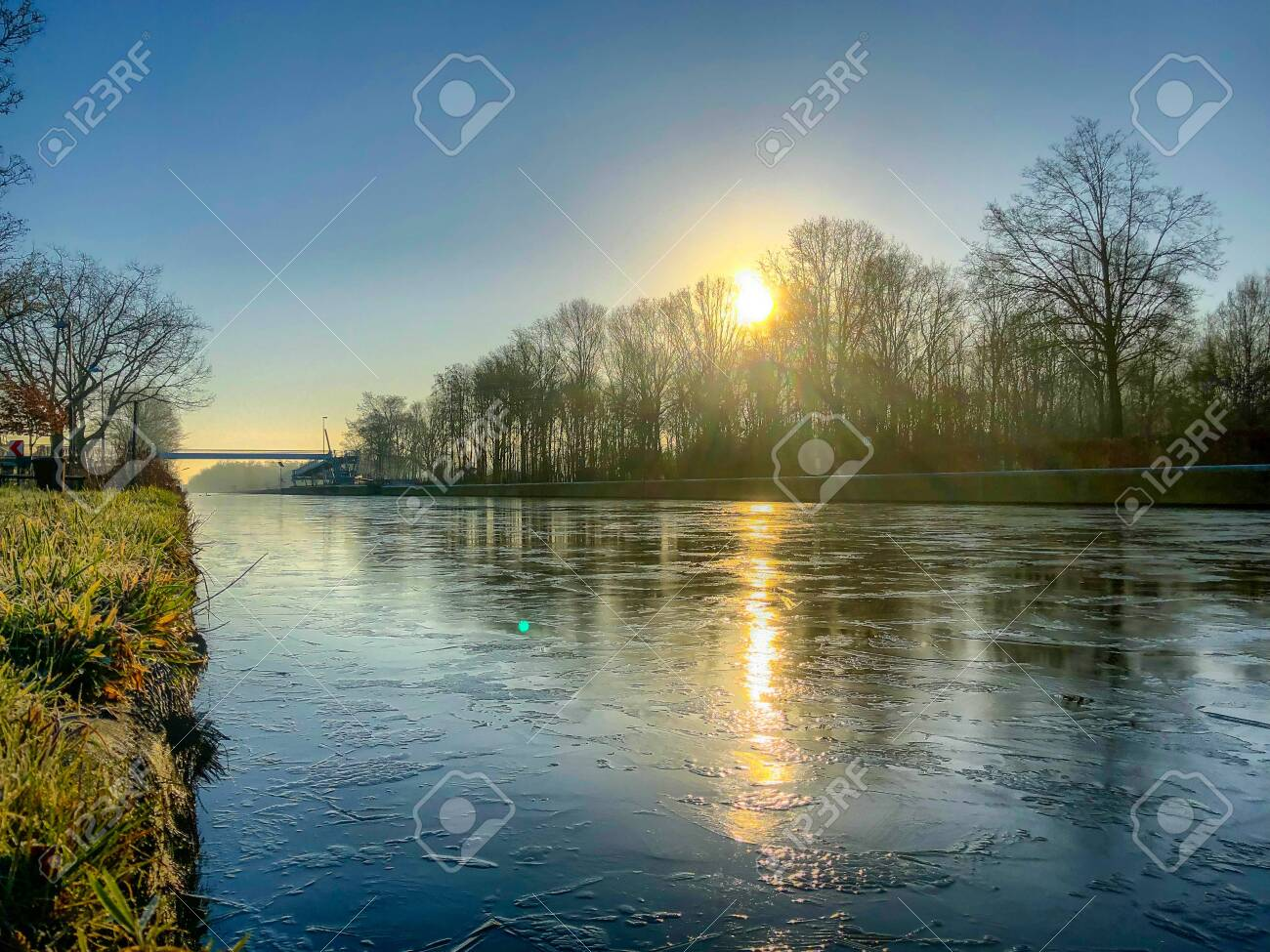 Dramatic and colorful sunrise or sunset over a beautiful landscape with a river or canal, treelined riverside and grass at sunrise creating a tranquile and quiet scenic nature background - 120944887