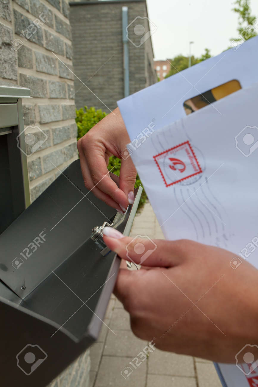 Close-up of womans hand holding envelope and inserting in or taking out of mailbox. High quality photo - 163074481