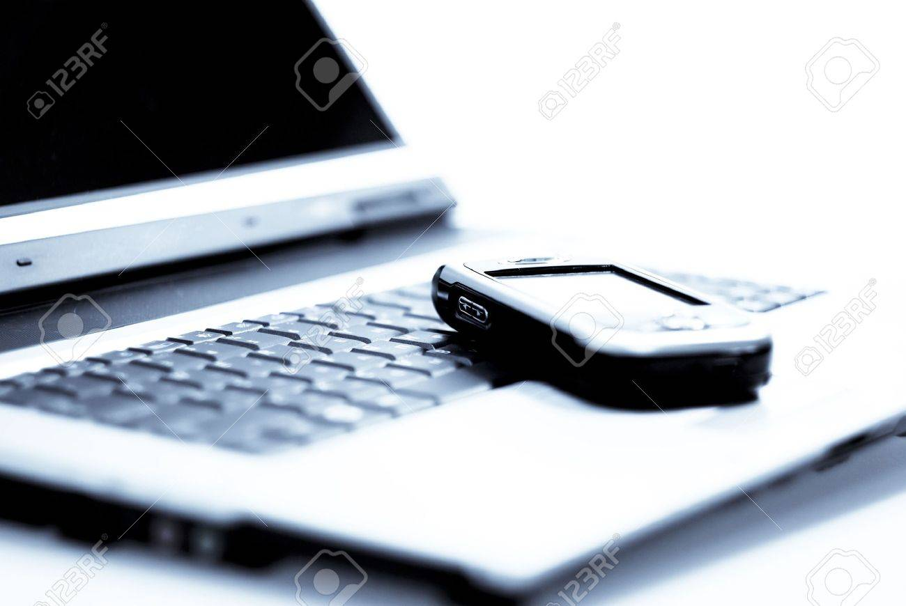 PDA (communicator) laying on laptop. Cold photofilter. Stock Photo - 3505097