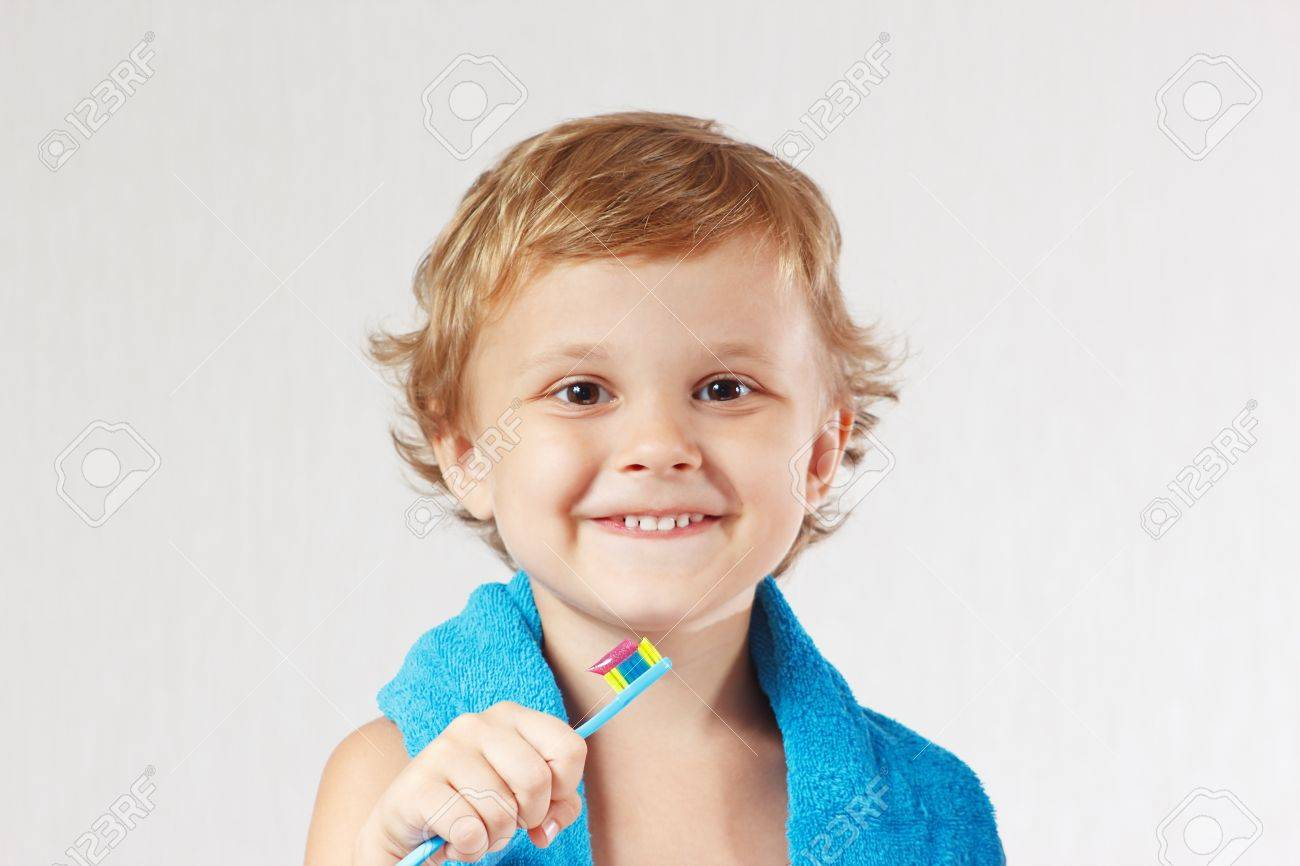 Young cute blond boy with toothbrush with pink toothpaste on a white background Standard-Bild - 14842680