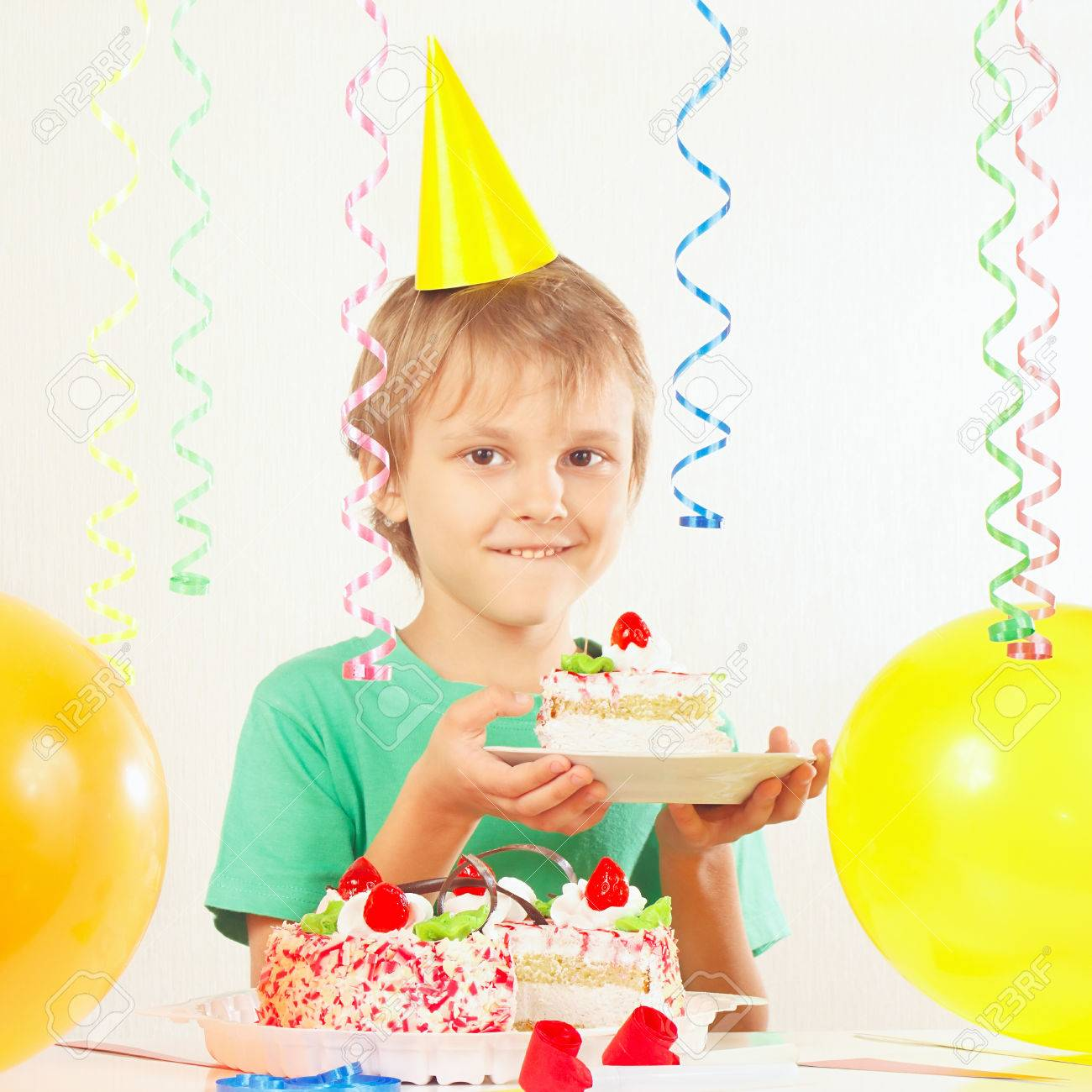 Little Kid In Holiday Hat With A Piece Of Birthday Cake And Balloons Stock Photo