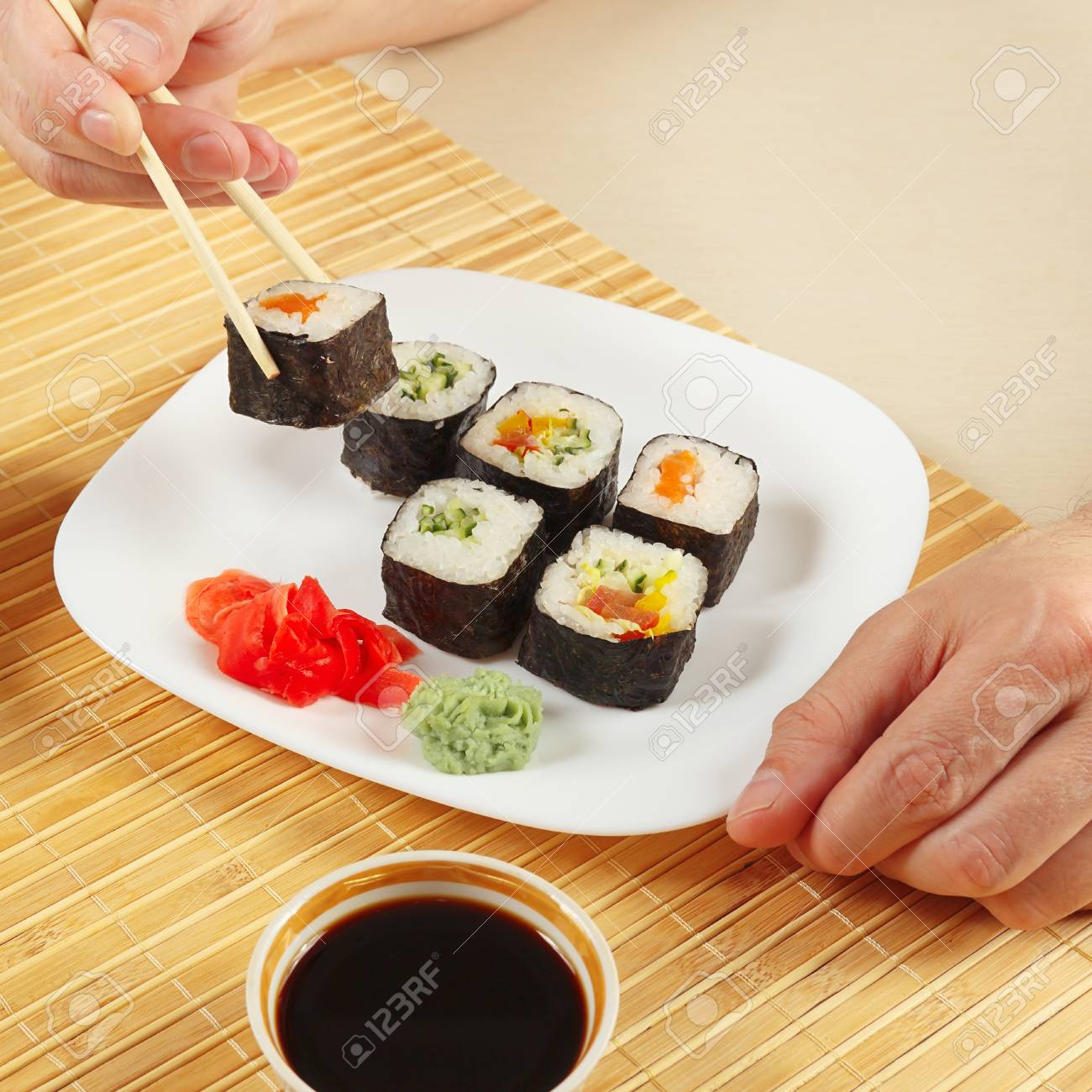 Hands Taking Sushi With Chopsticks Assorted Sushi With Ginger