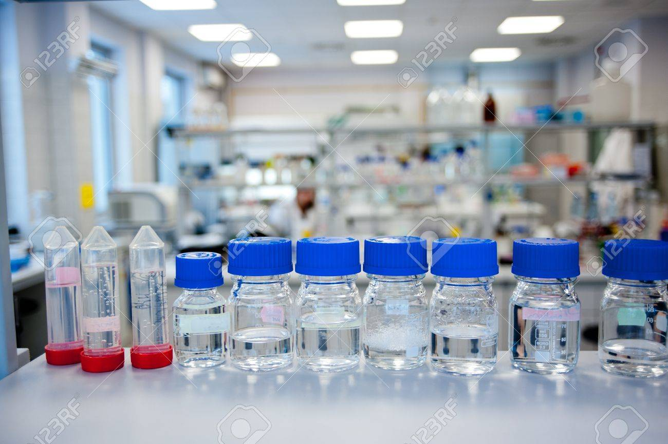 Chemicals reagents in a row in glass bottles placed at laboratory shelf  In background blurred chemical laboratory Stock Photo - 14191573