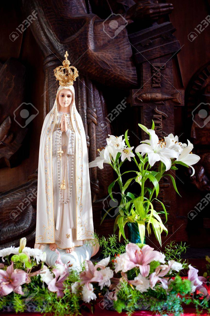 Statue of Virgin Mary from Lourdes in flowers and in golden crown Stock Photo - 15852358