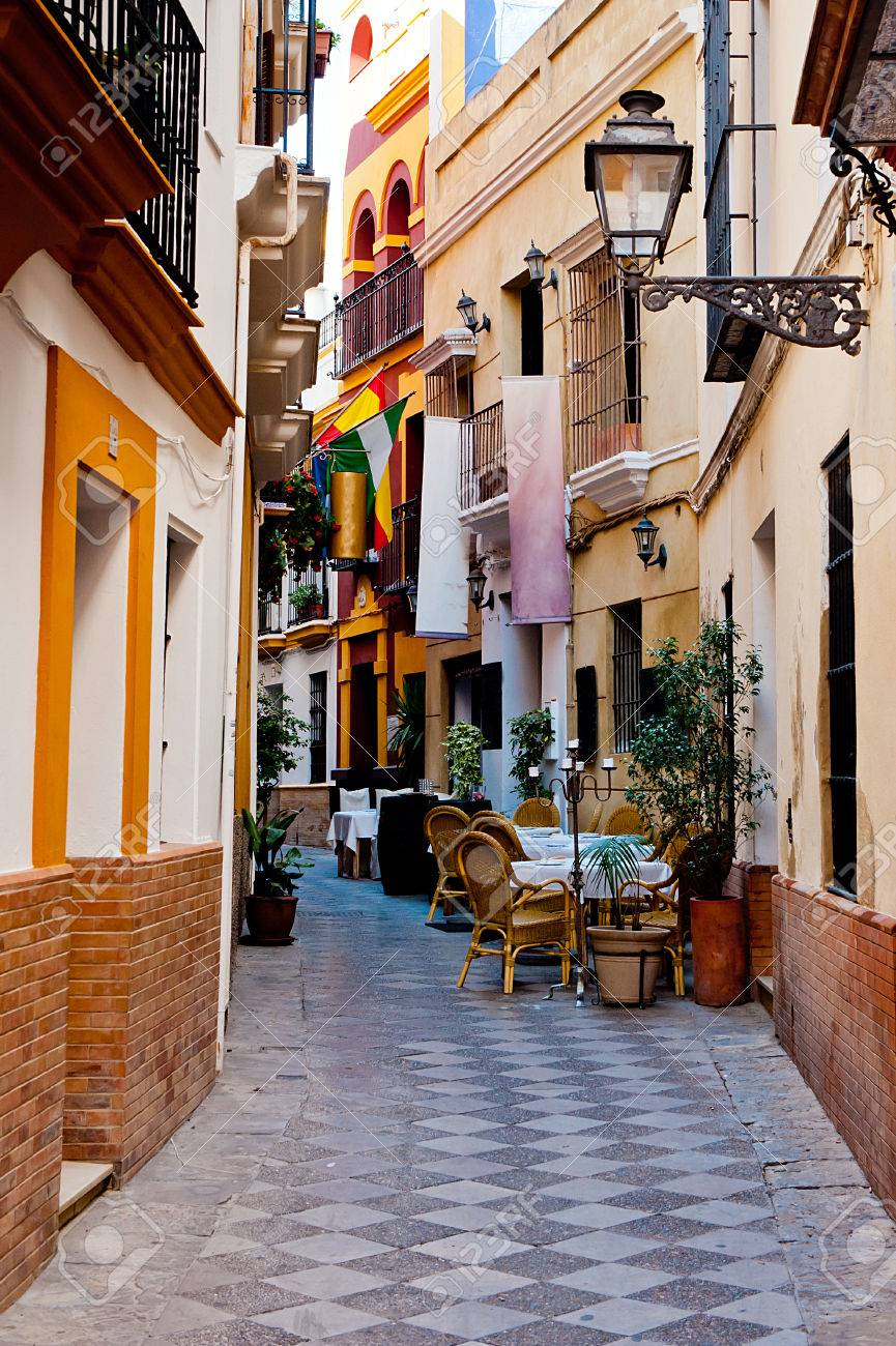 Spanish narrow alley with chairs and tables in Seville - 24969959