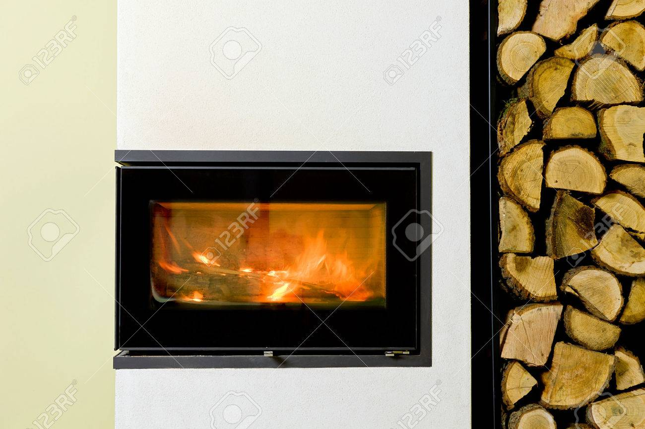 burning wood in fireplace insert. Wood stand with wood - 51152271