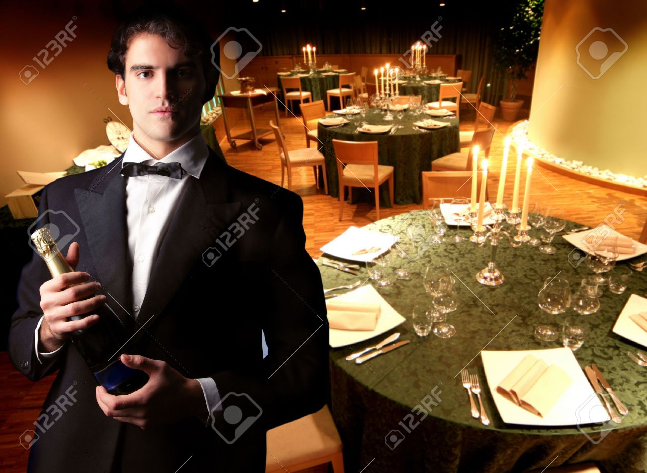 Waiter With Champagne Bottle In A Romantic Dining Room Stock Photo ...