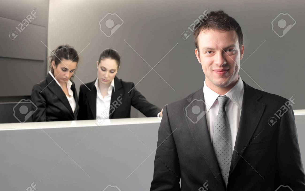 Smiling businessman with two receptionists on the background Stock Photo - 6898926
