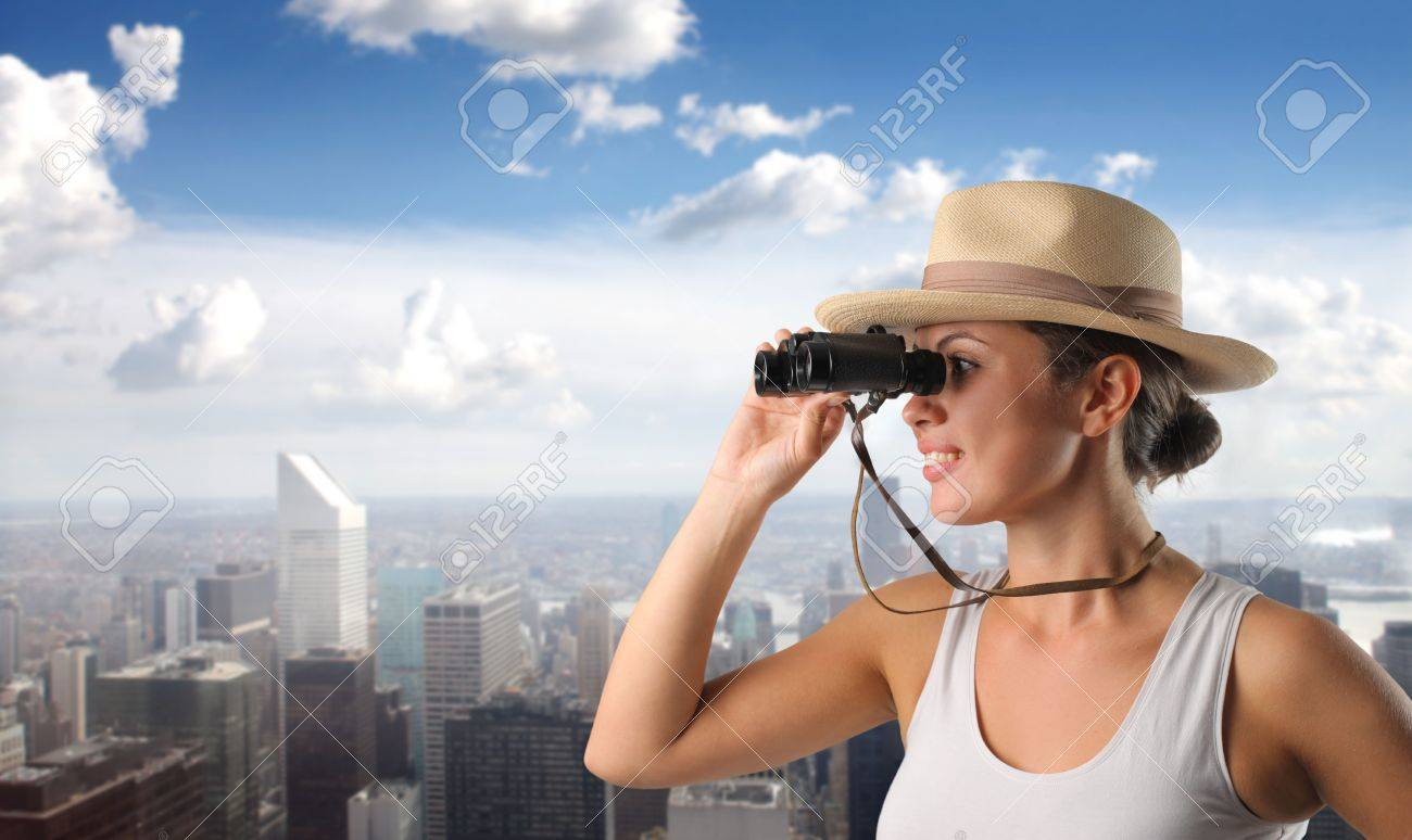Smiling woman using binoculars with cityscape on the background Stock Photo - 7875446