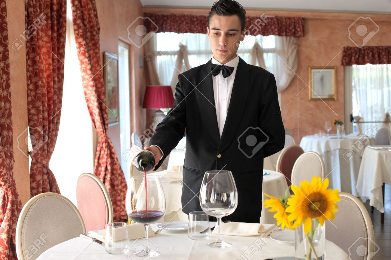 Young waiter serving some wine in a luxury restaurant - 7875459