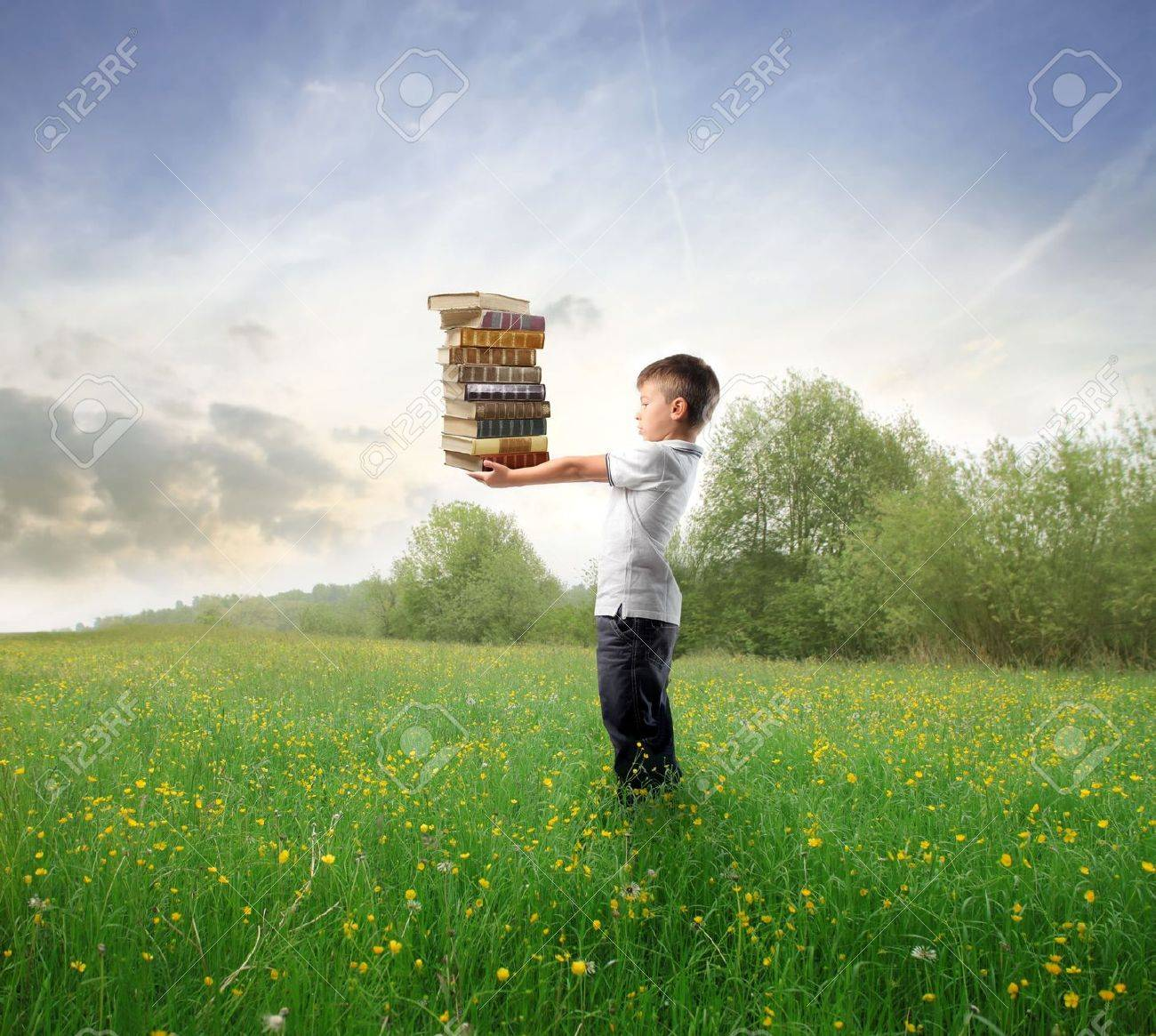 Child standing on a green meadowand holding some books - 8054408