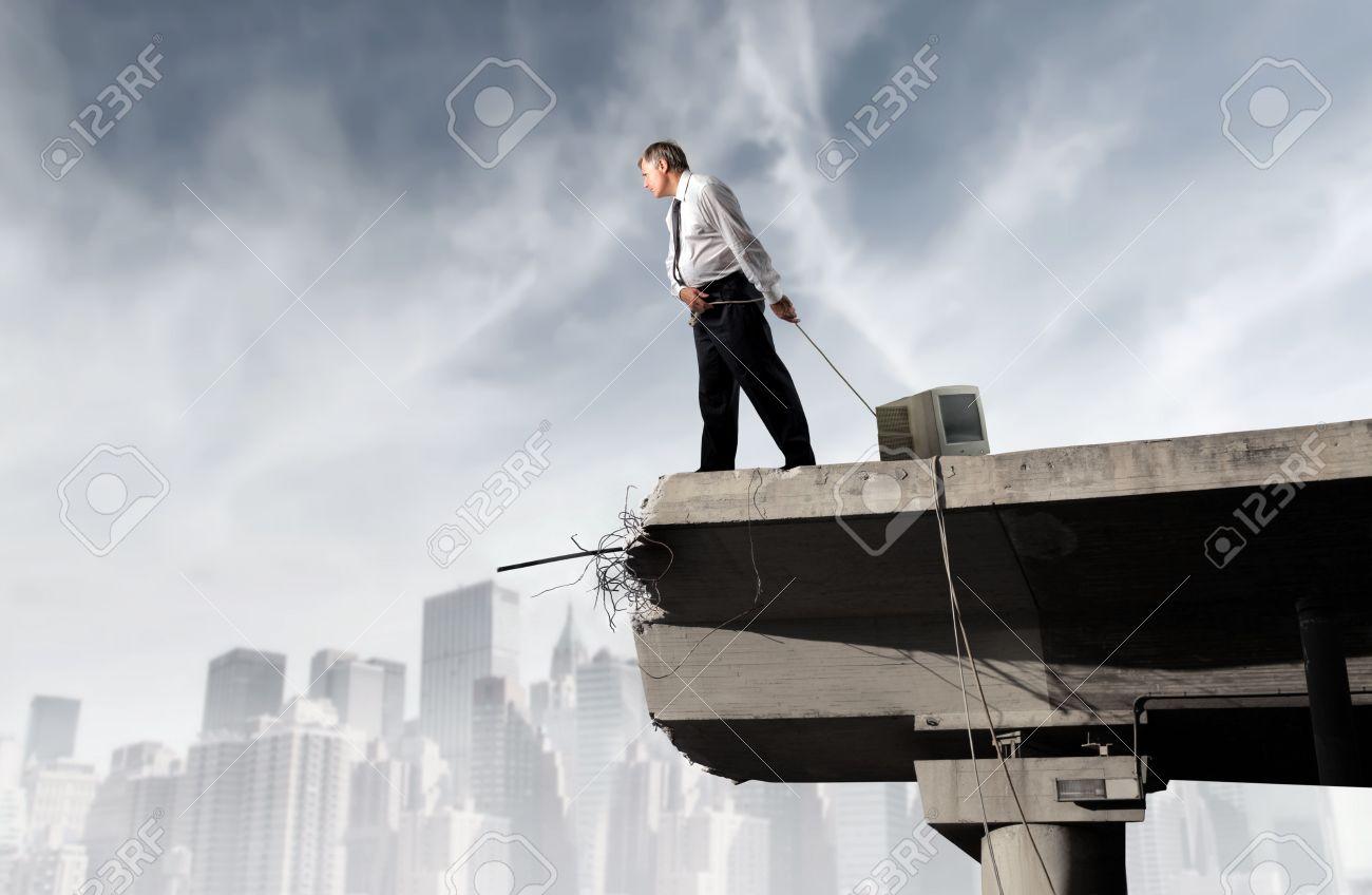 Businessman dragging a computer monitor on a bridge Stock Photo - 8054460