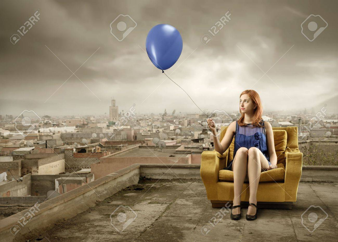 Elegant Woman Sitting On An Armchair And Holding A Balloon With Cityscape  On The Background Stock