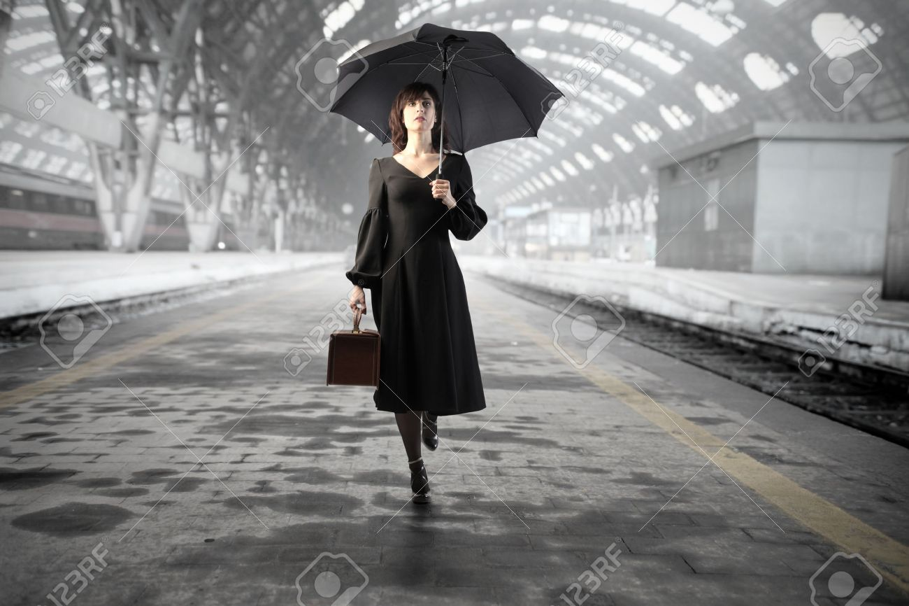 Beautiful Woman With Umbrella Standing On The Platform Of A Train