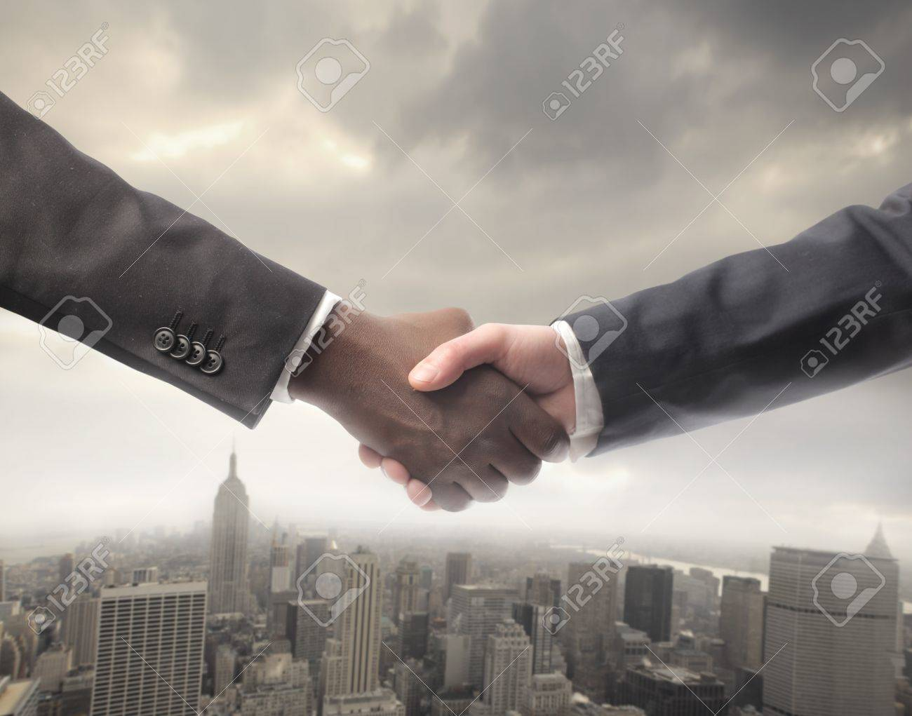 African businessman's hand shaking white businessman's hand with cityscape on the backgorund Stock Photo - 8736536