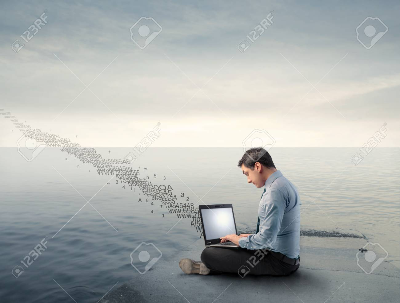 Businessman using a laptop on a wharf with numbers flying away from it Stock Photo - 8999973