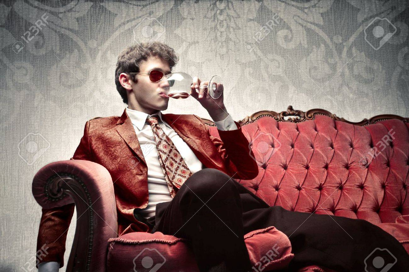 Young man sitting on a sofa and drinking a glass of wine Stock Photo - 10171766