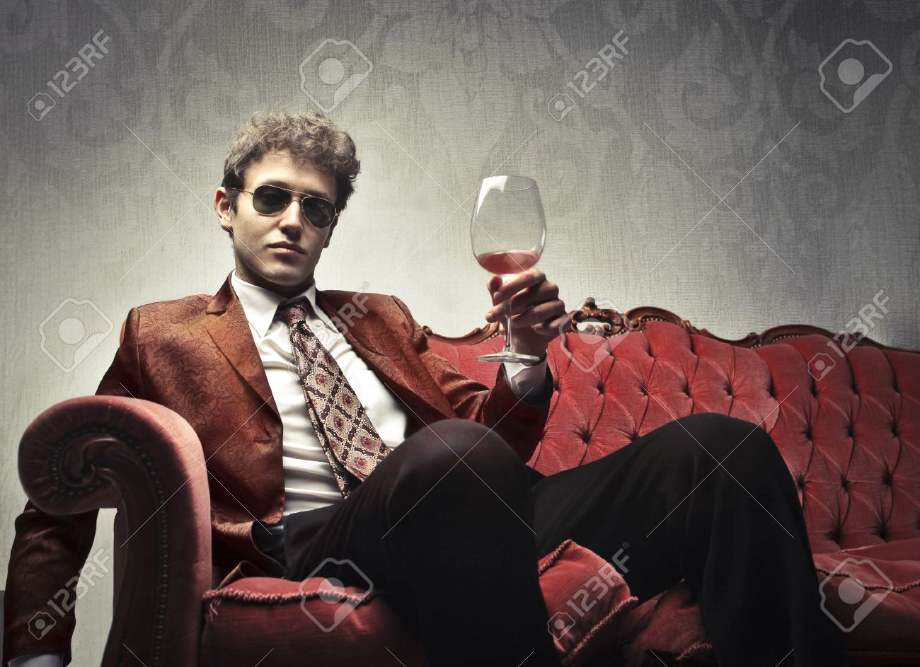 Elegant man sitting on a velvet sofa and holding a glass of wine Stock Photo - 10416614