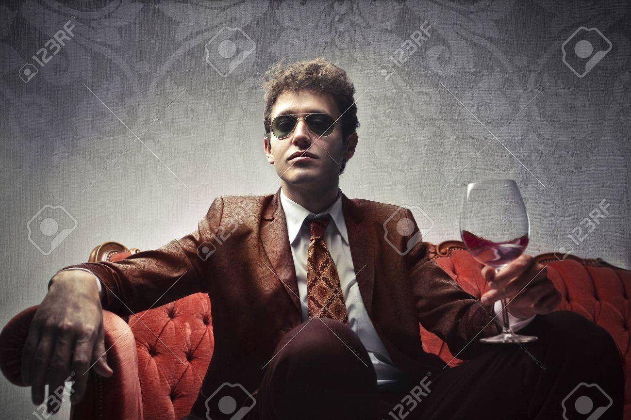 Elegant young man holding a glass of wine Stock Photo - 10416612