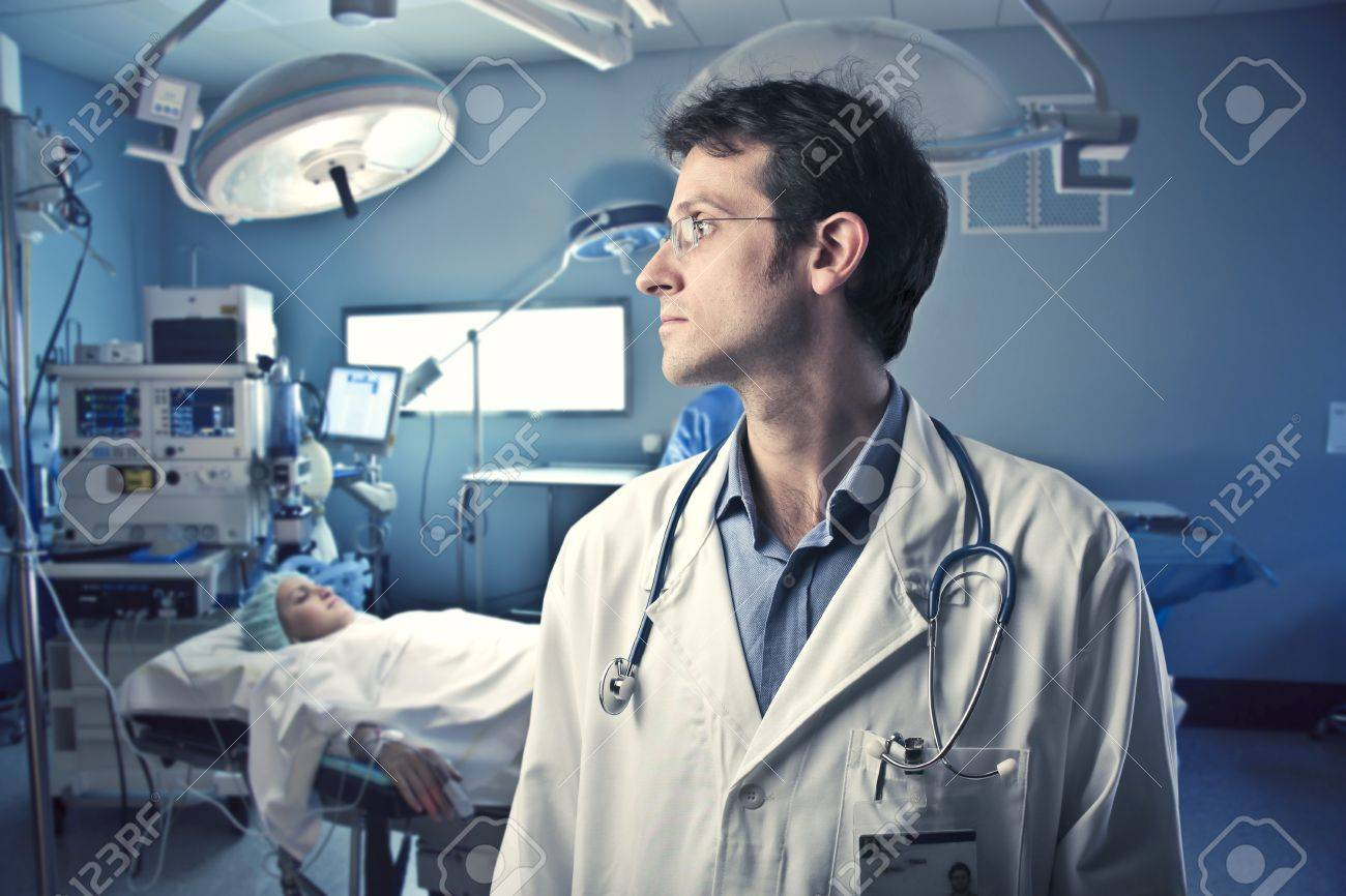 Surgeon in an operating room with patient in the background Stock Photo - 10805117