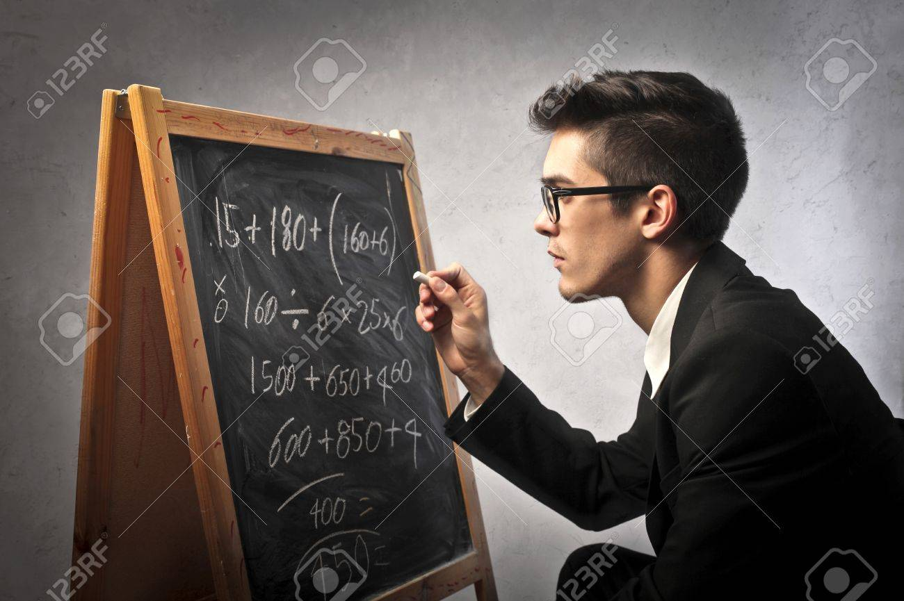 Businessman writing some calculations on a blackboard Stock Photo - 10916983