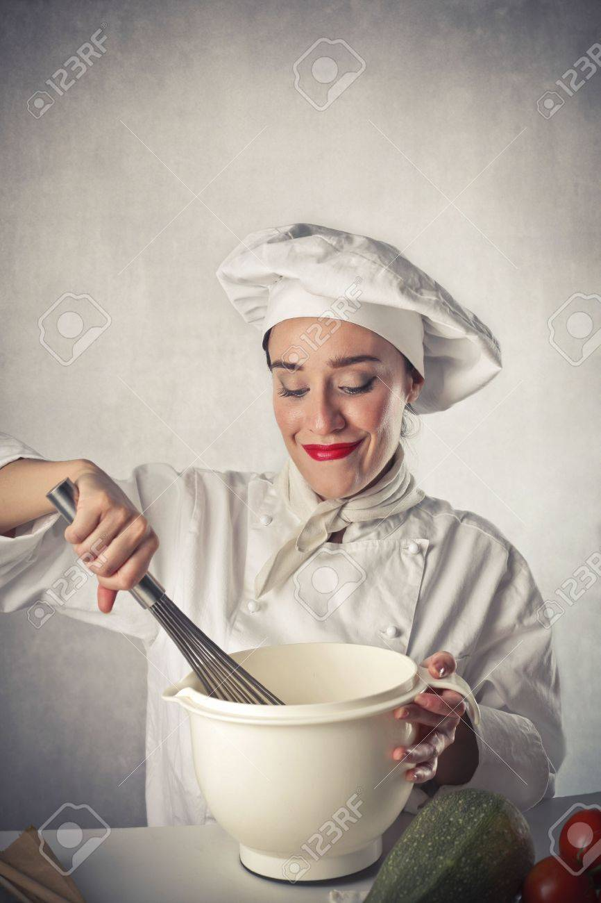 Smiling Female Cook Mixing Some Food Ingredients In A Bowl Stock Photo
